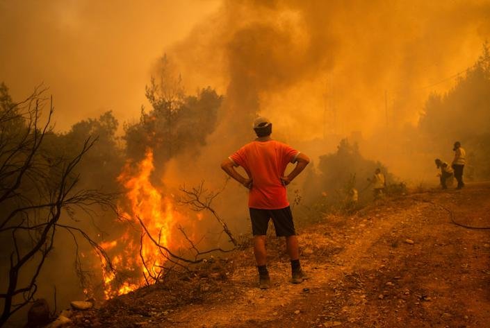 Under a cloud of smoke, a volunteer, with hands on hips, watches firefighters use a water hose near the burning blaze of a forest fire.