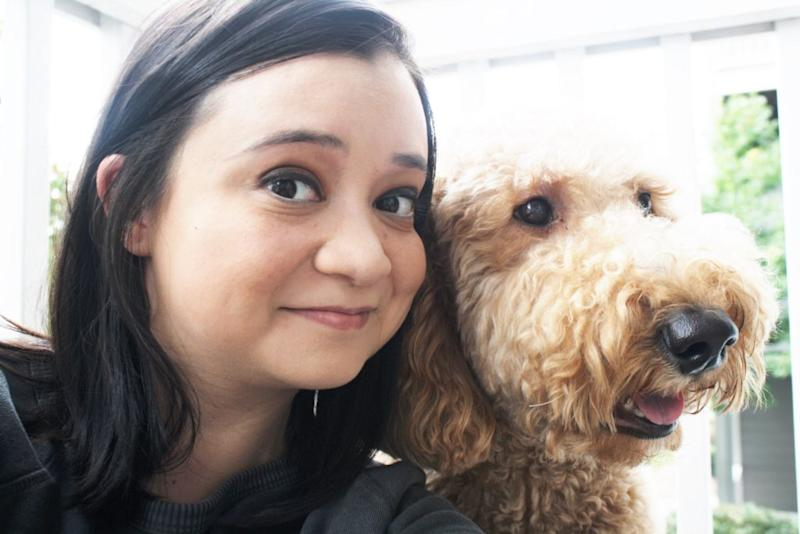 woman with black hair next to fluffy dog