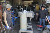 Jose Bonilla Jr., right, talks to an employee about cleaning a used industrial mixer for sale at the warehouse of his family's business, American Restaurant Supply in San Leandro, Calif., on Jan. 14, 2021. The pandemic has forced thousands of restaurants to permanently shut their doors as dining restrictions keep customers away. But the unprecedented closures have created a business boom for commercial auctioneers that buy and sell used restaurant equipment. (AP Photo/Terry Chea)