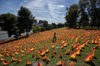 A woman walks among the Spanish flags placed in memory of coronavirus (COVID-19) victims in Madrid, Spain, Sunday, Sept. 27, 2020. An association of families of coronavirus victims has planted what it says are 53,000 small Spanish flags in a Madrid park to honor the dead of the pandemic. (AP Photo/Manu Fernandez)