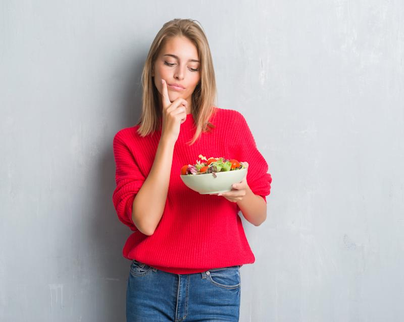 Beautiful young woman over grunge grey wall eating tomato salad serious face thinking about question, very confused idea