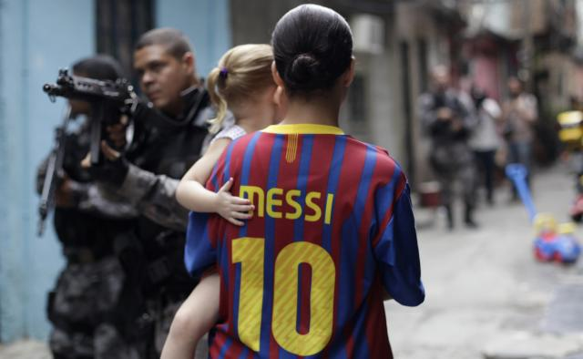 A woman wearing a Barcelona jersey with Lionel Messi's name holds a child as police officers take up positions during an operation at the Mare slums complex in Rio de Janeiro