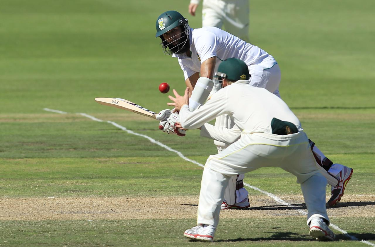 South Africa's batsman Hashim Amla, top, watches as Australia's fielder Steven Smith, bottom, fields off his shot on the third day of their 2nd cricket test match at St George's Park in Port Elizabeth, South Africa, Saturday, Feb. 22, 2014. (AP Photo/ Themba Hadebe)