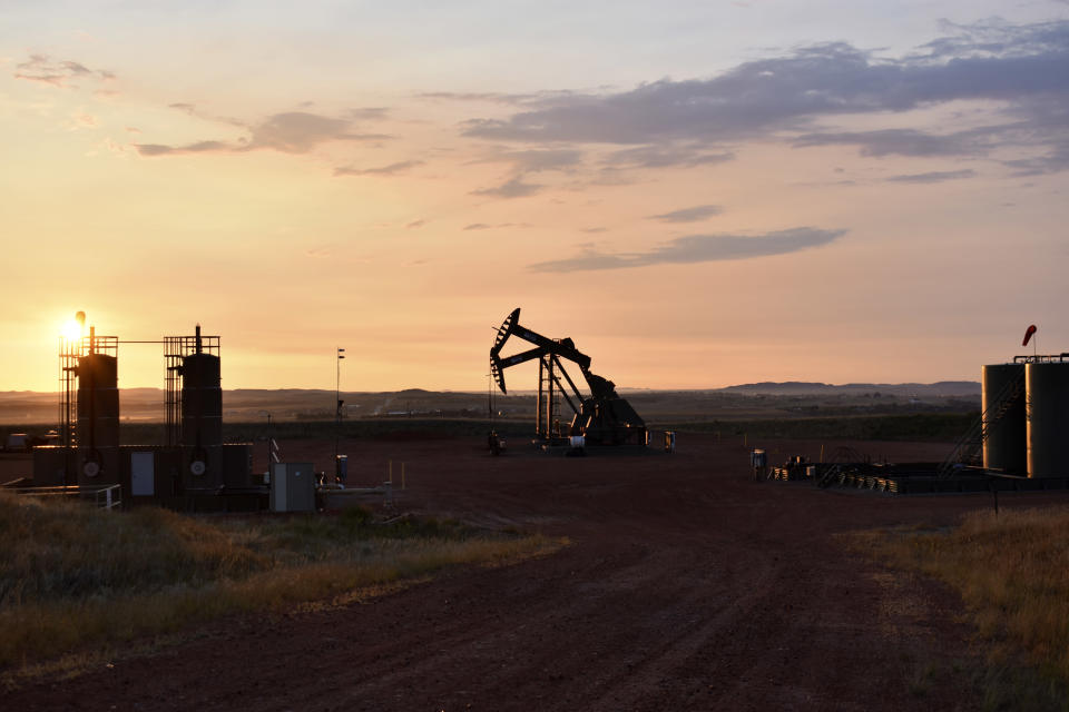 An oil well works at sunrise Aug. 25, 2021, in Watford City, N.D., part of McKenzie County. A drilling boom made McKenzie the fastest growing county in the U.S over the past decade, according to the 2020 census. (AP Photo/Matthew Brown)