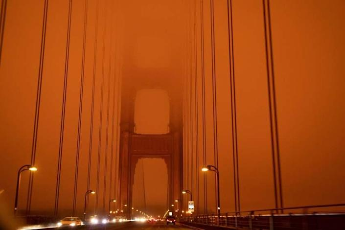 "Cars drive along the San Francisco Bay Bridge under an orange smoke filled sky at midday in San Francisco, California on September 9, 2020. - More than 300,000 acres are burning across the northwestern state including 35 major wildfires, with at least five towns ""substantially destroyed"" and mass evacuations taking place. (Photo by Harold POSTIC / AFP) (Photo by HAROLD POSTIC/AFP via Getty Images)"