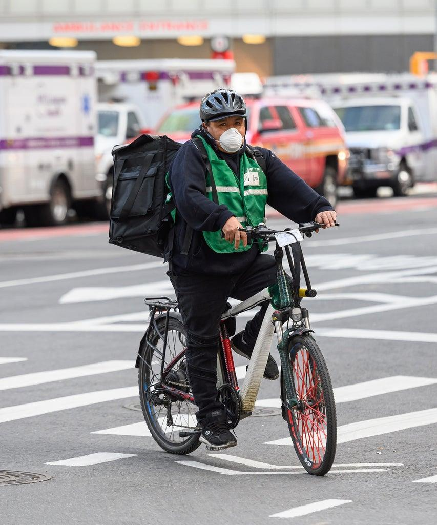 NEW YORK, NEW YORK – MAY 05: A delivery man wears a protective face mask while riding a bicycle in Kips Bay during the coronavirus pandemic on May 5, 2020 in New York City. COVID-19 has spread to most countries around the world, claiming over 258,000 lives with over 3.7 million infections reported. (Photo by Noam Galai/Getty Images)