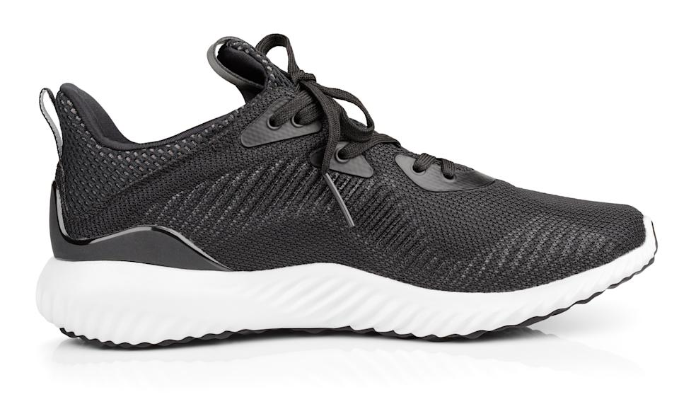Single new unbranded black sport running shoe, sneakers or trainers isolated on white background with clipping path