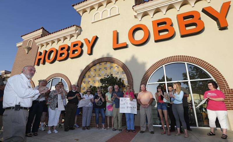 CLARIFIES THAT REV. PRESCOTT WAS HOLDING A VIGIL IN OPPOSITION TO THE SUPREME COURT RULING - Rev. Bruce Prescott, left, leads a vigil outside a Hobby Lobby store in Edmond, Okla., Monday, June 30, 2014, in opposition to the Supreme Court's decision that some companies like the Oklahoma-based Hobby Lobby chain of arts-and-craft stores can avoid the contraceptives requirement in President Barack Obama's health care overhaul, if they have religious objections. (AP Photo/Sue Ogrocki)