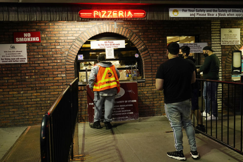 People line up to order take-out pizzas at L&B Spumoni Gardens, Sunday, Oct. 4, 2020, in the Brooklyn borough of New York. The restaurant's indoor dining is closed due to the limitations of serving at 25% capacity, and is also being renovated. But the large outdoor seating area was busy at dinner time Sunday. Since it's in a New York city zip code experiencing a rise in the number of coronavirus cases, the restaurant may be forced to close all but its takeout service and delivery service. (AP Photo/Kathy Willens)