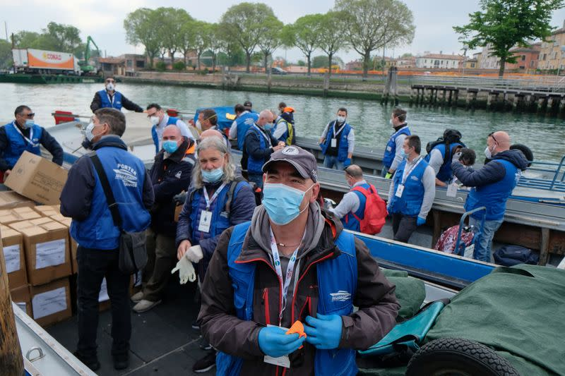 Volunteers distribute protective face masks to the people to contain the spread of the coronavirus disease (COVID-19)