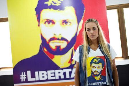 Lilian Tintori, wife of jailed Venezuelan opposition leader Leopoldo Lopez, poses for a picture in front of a poster depicting her husband at the office of the party Popular Will (Voluntad Popular) in Caracas, Venezuela January 18, 2017. REUTERS/Carlos Garcia Rawlins