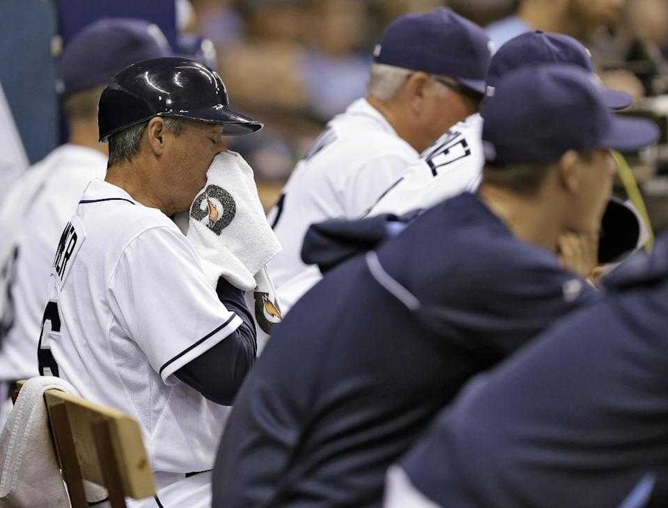 Tampa Bay Rays third base coach Tom Foley wipes his face after word spread through the Rays dugout that team special advisor Don Zimmer had passed away. The Rays were playing the Miami Marlins during an interleague baseball game Wednesday, June 4, 2014, in St. Petersburg, Fla. (AP Photo/Chris O'Meara)