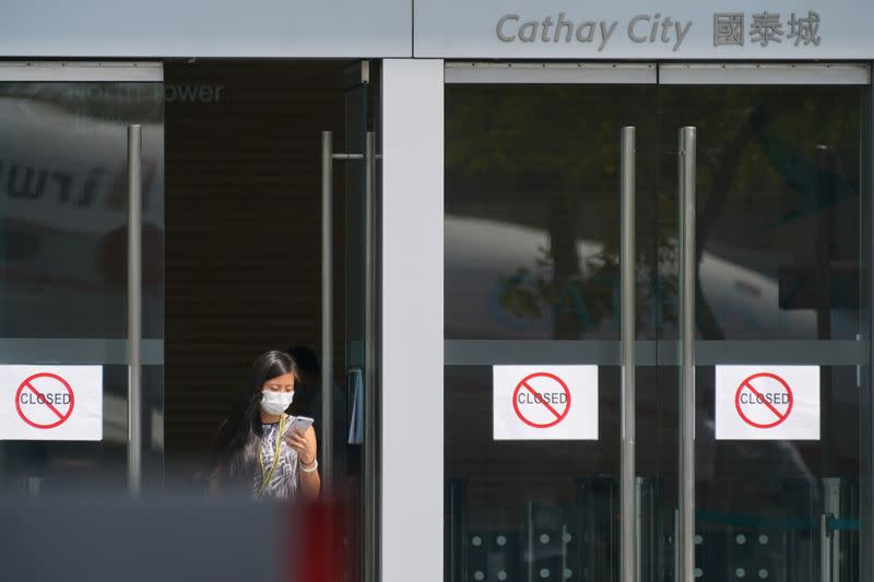 Woman wearing a mask following the coronavirus disease (COVID-19) outbreak, walks out of Cathay City, the headquarters of Cathay Pacific, in Hong Kong