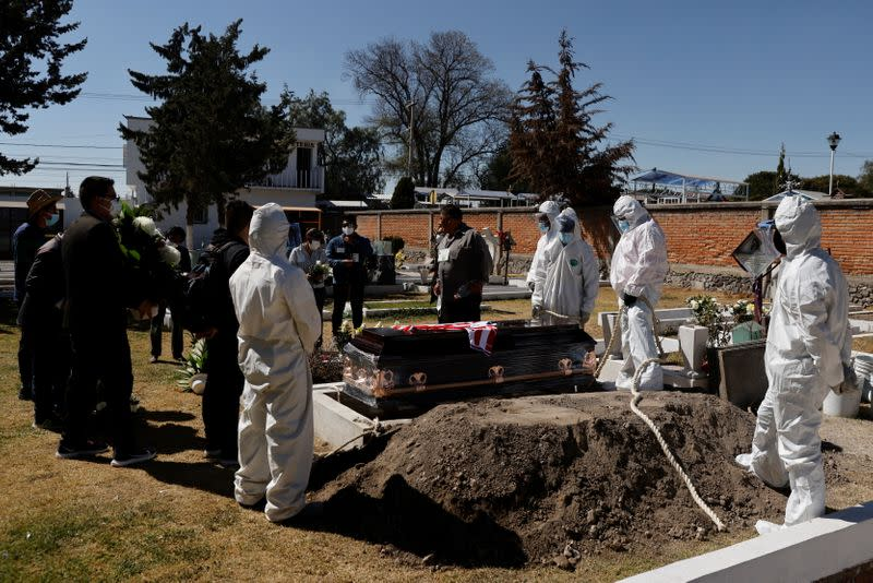 Family members say their last goodbyes to their relative Emilio Valencia, who died from the coronavirus disease (COVID-19), at a local cemetery on the outskirts of Mexico City