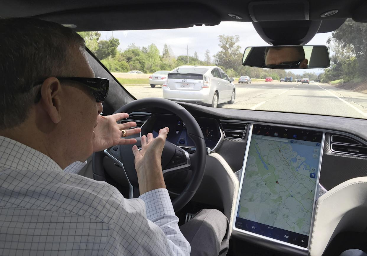 Reuters journalist Paul Ingrassia sits in the drivers seat of a Tesla S-Type in Autopilot mode in San Francisco, California, U.S., April 7, 2016.   To match Special Report AUTOS-DRIVERLESS/ REUTERS/Alexandria Sage