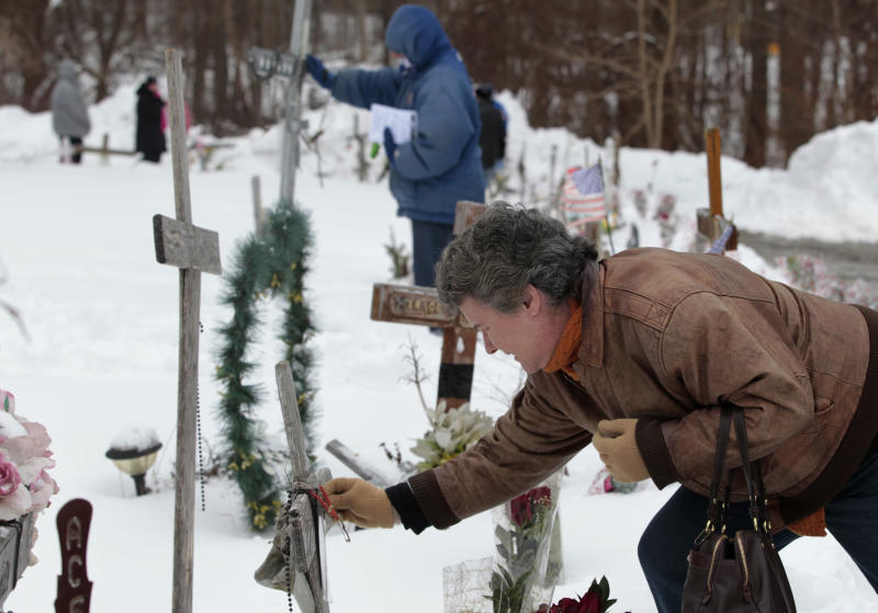 Tonda Daniels, of South Kingstown, R.I., front, places an ornament on a makeshift memorial to her fallen sister Lori Durante at the site of the Station nightclub fire, Sunday, Feb. 17, 2013, in West Warwick, R.I. The Station Fire Memorial Foundation unveiled final plans to build a permanent memorial at the site during ceremonies Sunday. The 2003 blaze took the lives of 100 people. (AP Photo/Steven Senne)