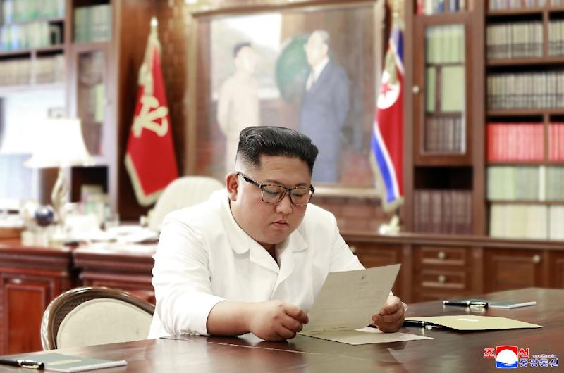 This undated and unlocated picture released from North Korea's official Korean Central News Agency (KCNA)on June 23, 2019 shows North Korean leader Kim Jong Un reading a personal letter from President of the United States of America Donald Trump