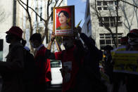 Myanmar people living in Japan and supporters march with a portrait of detained Myanmar's ousted leader Aung San Suu Kyi during a protest in Sunday, Feb. 14, 2021, in Tokyo. Thousands of people from Myanmar living in Japan have marched in downtown Tokyo to protest the military coup back home. (AP Photo/Eugene Hoshiko)