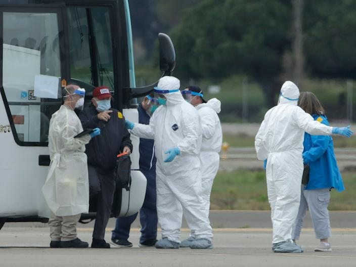 Passengers from the Grand Princess, a cruise ship carrying multiple people who have tested positive for COVID-19, exit a bus before boarding a chartered plane in Oakland, Calif., Tuesday, March 10, 2020. The passengers on the flight are going to San Antonio to be quarantined at Lackland Air Force Base.