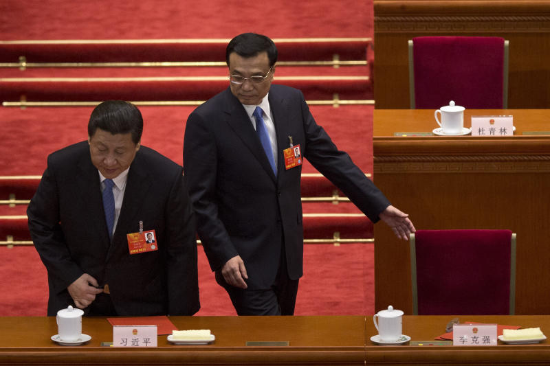 Chinese President Xi Jinping, left, and Premier Li Kiqiang, right, get to their seats during a plenary session of the NPC held in Beijing's Great Hall of the People, China, Saturday, March 16, 2013. China's new leaders turned Saturday to veteran technocrats with greater international experience to staff a Cabinet charged with overhauling a slowing economy and pursuing a higher global profile without triggering opposition. (AP Photo/Alexander F. Yuan)