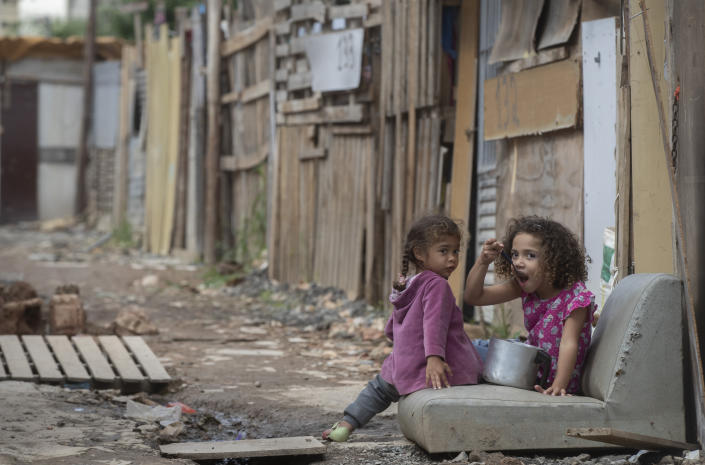 A child eats from a pot as she eyes the camera in the Penha Brasil favela where families have started relocating during the coronavirus pandemic in Sao Paulo, Brazil, Saturday, May 15, 2021. Over 200 families live in the Penha Brasil community, one of the new slums that are sprouting up around Brazil's largest city, inhabited mostly by newly unemployed workers who lost their jobs and homes as a result of the pandemic. (AP Photo/Andre Penner)