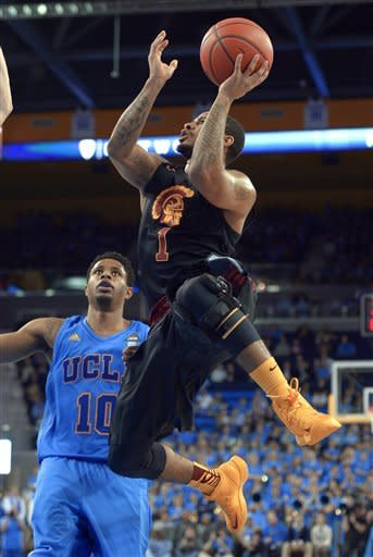 Southern California guard Jio Fontan, right, puts up a shot as UCLA guard Larry Drew II defends during the first half of their NCAA college basketball game, Wednesday, Jan. 30, 2013, in Los Angeles. (AP Photo/Mark J. Terrill)