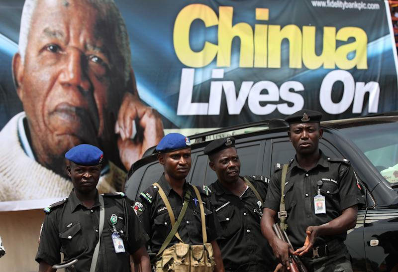 Police officers stand guards under a giant poster of late author Chinua Achebe, as part of an event in Awka, Nigeria, Wednesday, May 22, 2013. People gathered Wednesday to celebrate the life of author Chinua Achebe, who died in March at the age of 82. His family plans to bury the literary icon Thursday in his home village of Ogidi. (AP Photo/Sunday Alamba)