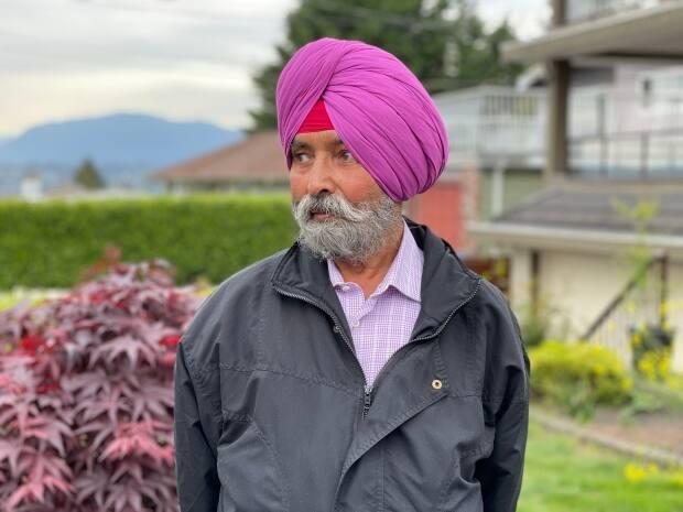 Paramjit Basanti stands outside the Surrey, B.C., home he shares with several other members of his extended family.  (Christian Amundson/CBC - image credit)