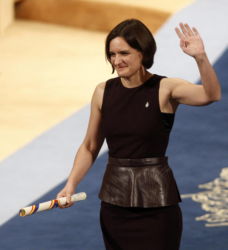 "FILE - In this Friday Oct. 23, 2015 file photo, Esther Duflo of France waves after receiving the Princess of Asturias award for Social Sciences from Spain's King Felipe VI at a ceremony in Oviedo, northern Spain. The 2019 Nobel prize in economics has been awarded to Abhijit Banerjee, Esther Duflo and Michael Kremer ""for their experimental approach to alleviating global poverty."" The Royal Swedish Academy of Sciences announced the prize on Monday Oct. 14, 2019. (AP Photo/Jose Vicente, File)"