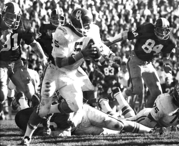 In this Nov. 15, 1975 file photo, University of Oklahoma quarterback Steven Davis (5) sweeps for a 15-yard gain against Missouri in Columbia, Mo. A University of Oklahoma official says the starting quarterback for Oklahoma's national championship teams in 1974 and 1975 is one of two men killed when a small plane slammed into a house in northern Indiana. St. Joseph County Coroner Randy Magdalinski identified the victims of Sunday's march 17, 2013 crash as 60-year-old Steven Davis and 58-year-old Wesley Caves, both of Tulsa, Okla. (AP Photo/The Oklahoman, Jim Arego, File)