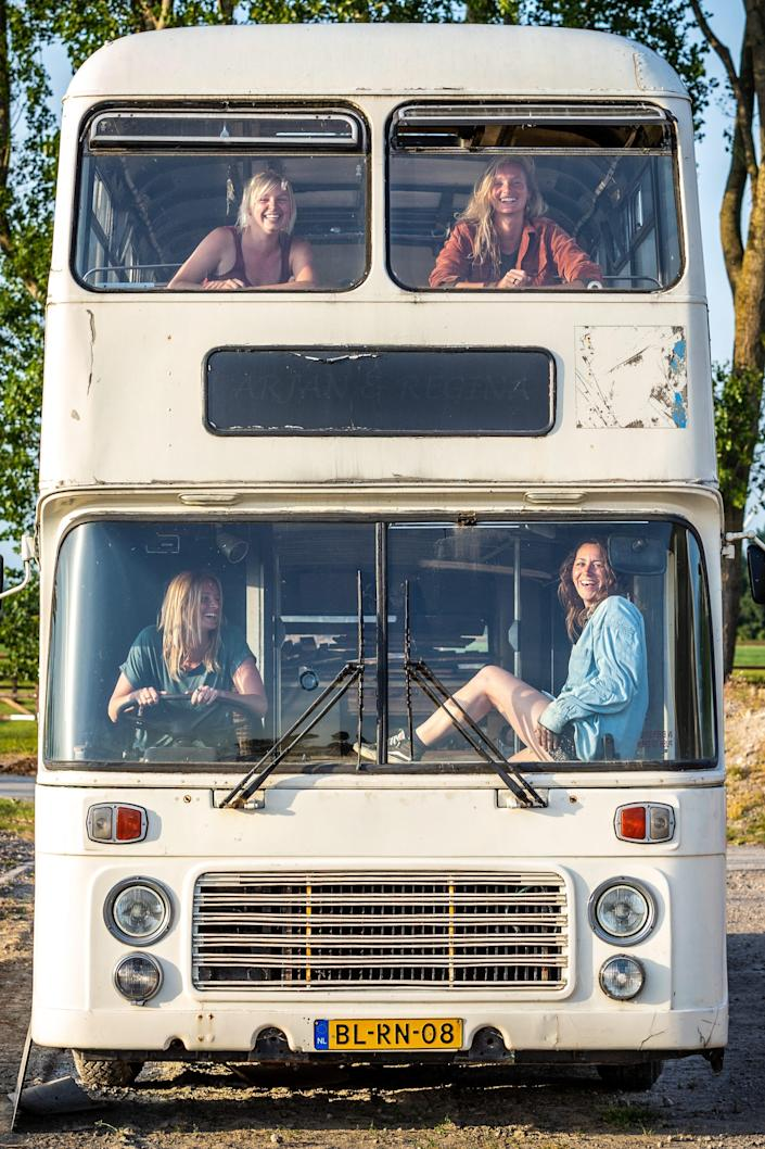 The four women sitting in the front windows of the double decker bus