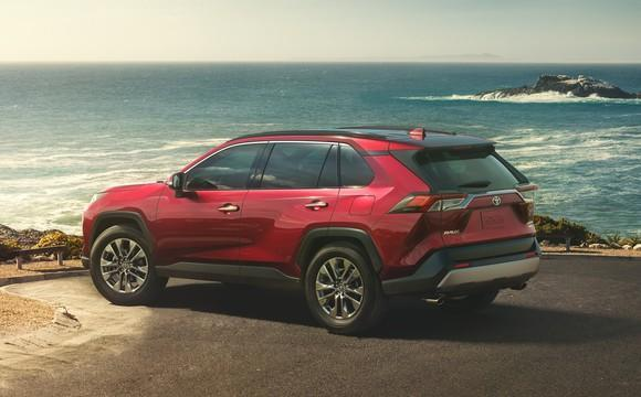 A red 2019 Toyota RAV4, a compact crossover SUV, parked in an oceanfront parking lot.