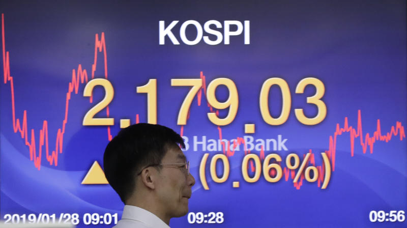 A currency trader walks by the screen showing the Korea Composite Stock Price Index (KOSPI) at the foreign exchange dealing room in Seoul, South Korea, Monday, Jan. 28, 2019. Markets are higher in Asia after President Donald Trump ended the partial U.S. government shutdown. (AP Photo/Lee Jin-man)