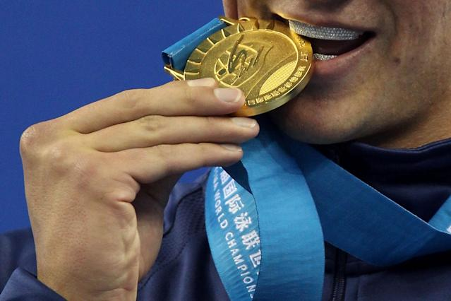 SHANGHAI, CHINA - JULY 26: A detail of Ryan Lochte of the United States as he bites his gold medal with a grill in his moutch after the Men's 200m Freestyle Final during Day Eleven of the 14th FINA World Championships at the Oriental Sports Center on July 26, 2011 in Shanghai, China. (Photo by Clive Rose/Getty Images)