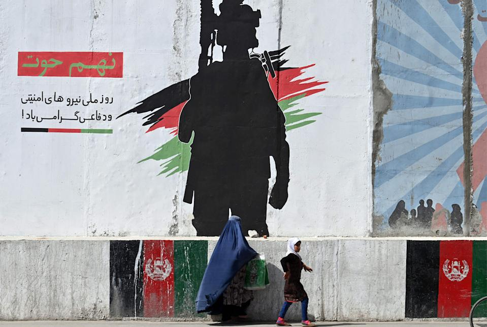 A burqa-clad woman and a girl walk past a mural depicting an Afghan National Army soldier, in Kabul on June 10, 2021.