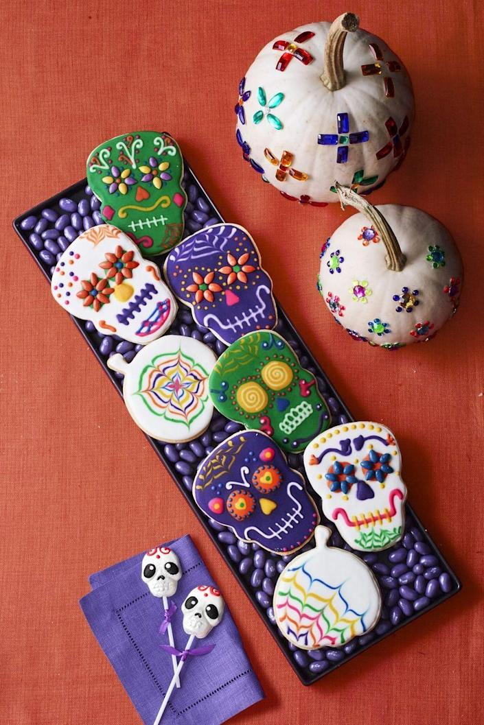 """<p>Don't be intimidated by the intricate designs on these cookies — the recipe tells you simple ways to channel your inner artist.</p><p><strong><em><a href=""""https://www.womansday.com/food-recipes/food-drinks/a23569445/cookie-skulls-and-pumpkin-sugar-cookie-cutouts-recipe/"""" rel=""""nofollow noopener"""" target=""""_blank"""" data-ylk=""""slk:Get the Cookie Skulls and Pumpkin Sugar Cookies recipe."""" class=""""link rapid-noclick-resp"""">Get the Cookie Skulls and Pumpkin Sugar Cookies recipe. </a></em></strong></p>"""