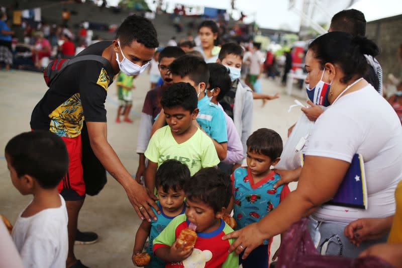 Venezuelan migrant children line up inside a coliseum where a temporary camp has been set up, after fleeing their country due to military operations, according to the Colombian migration agency, in Arauquita