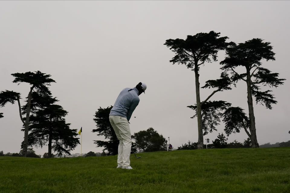 Tony Finau chips to the green on the 10th hole during the first round of the PGA Championship golf tournament at TPC Harding Park Thursday, Aug. 6, 2020, in San Francisco. (AP Photo/Jeff Chiu)