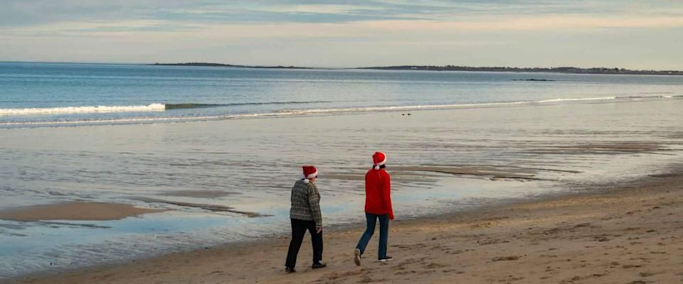 Rear view of a couple of women walking along the ocean shore in Maine USA. They wear father Christmas hat in December.