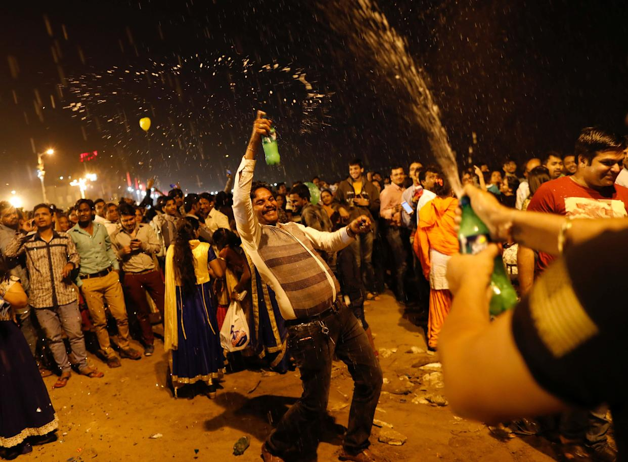 People dance during New Year's celebrations on a beach in Mumbai, India on January 1, 2018. (Photo: Danish Siddiqui / Reuters)
