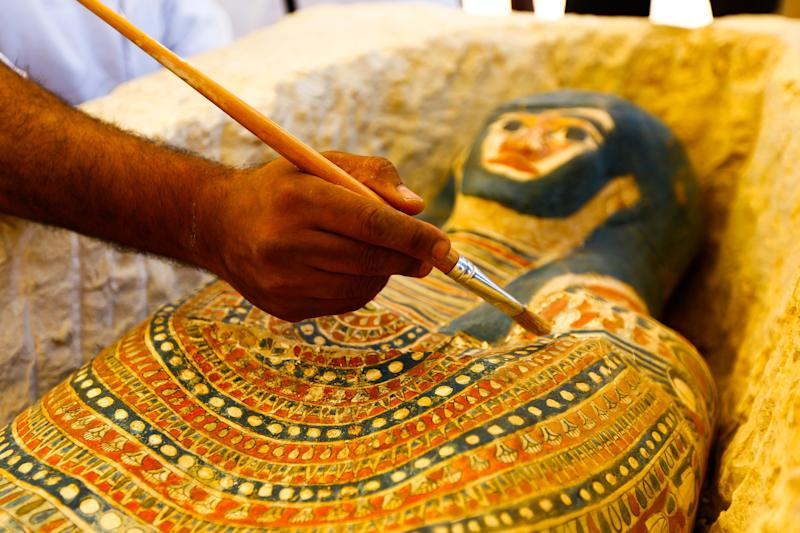 An Egyptian archaeological expert works on a newly discovered Pharaonic sarcophagus, which according to Egyptian authorities dates back to the Middle Kingdom of Egypt, discovered near the Bent Pyramid of Sneferu.