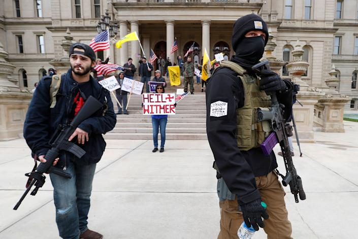Protesters carry rifles near the steps of the Michigan State Capitol in Lansing on April 15. Flag-waving, honking protesters drove past the Capitol on Wednesday to demonstrate against Gov. Gretchen Whitmer's social distancing measures to slow the spread of the coronavirus. (Photo: ASSOCIATED PRESS)