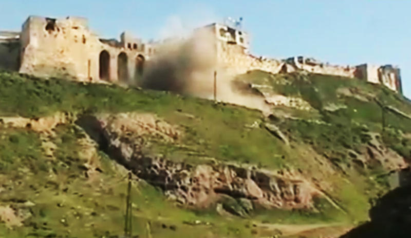 This image made from amateur video and released by Ugarit News Wednesday, March 21, 2012, purports to show a castle being shelled in Hama, Syria. The U.N. Security Council has strongly backed international envoy Kofi Annan's proposals to end the yearlong bloodshed in Syria. (AP Photo/Shaam News Network via APTN) THE ASSOCIATED PRESS CANNOT INDEPENDENTLY VERIFY THE CONTENT, DATE, LOCATION OR AUTHENTICITY OF THIS MATERIAL. TV OUT
