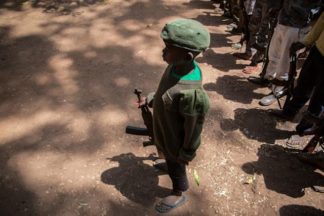 A newly-released child soldier stands with his rifle during a ceremony on Feb. 7, 2018.
