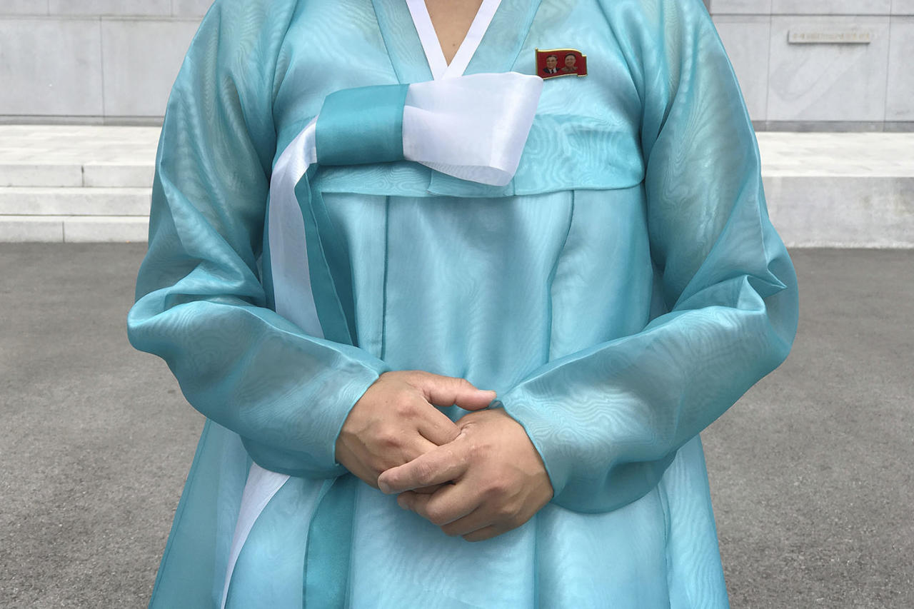 <p>A factory guide in a traditional Korean dress with the faces of the late North Korean leaders Kim Il Sung and Kim Jong Il pinned above her heart on the left of her dress, speaks to visiting media in Pyongyang, North Korea, July 26, 2017. (Photo: Wong Maye-E/AP) </p>