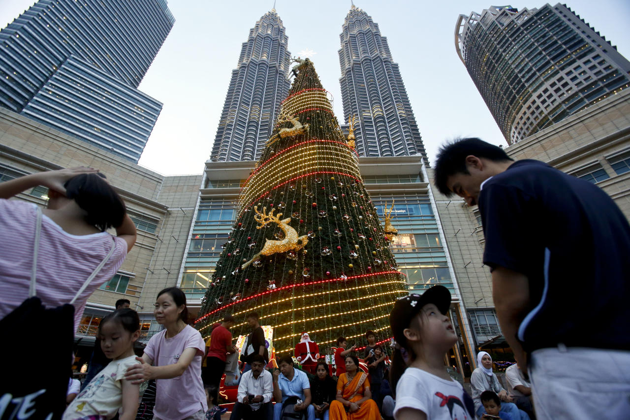 Tourists walk past and sit in front of a Christmas tree outside Malaysia's landmark building, Petronas Twin Towers in Kuala Lumpur, Malaysia, Wednesday, Dec. 13, 2017. Shopping malls in the Muslim-dominated nation have been decorated with Christmas trees, Santa Claus figures and illuminations to attract year-end shoppers. (AP Photo/Sadiq Asyraf)