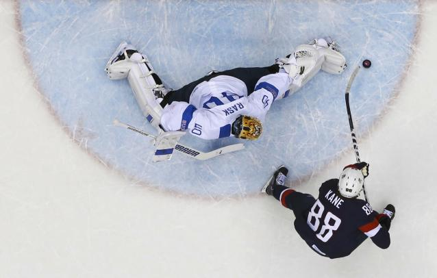 Finland's goalie Tuukka Rask (L) stops Team USA's Patrick Kane on a penalty shot during the first period of their men's ice hockey bronze medal game at the Sochi 2014 Winter Olympic Games February 22, 2014. REUTERS/Mark Blinch (RUSSIA - Tags: SPORT ICE HOCKEY OLYMPICS)