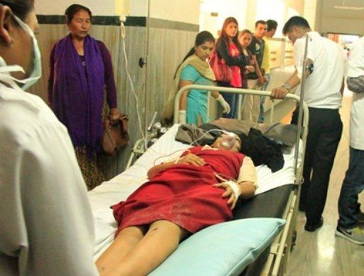 A flight attendant who survived a plane crash in northern Nepal receives medical attention at a hospital in Pokhara. The small plane crashed near a treacherous high-altitude airport, killing 15 people while six others miraculously survived