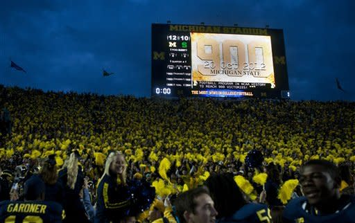Michigan players celebrate by the student section of Michigan Stadium after an NCAA college football game against Michigan State, Saturday, Oct. 20, 2012, in Ann Arbor, Mich. Michigan won 12-10, claiming the program's 900th victory, the most wins in college football. (AP Photo/Tony Ding)