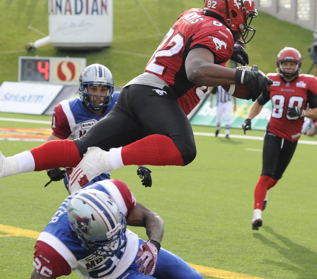 Calgary Stampeders' Nik Lewis, top, leaps over Montreal Alouettes' Michael Carter and into the end zone for a touchdown during second half CFL acton in Calgary on Friday July 1st, 2011. CFL PHOTO-Larry MacDougal